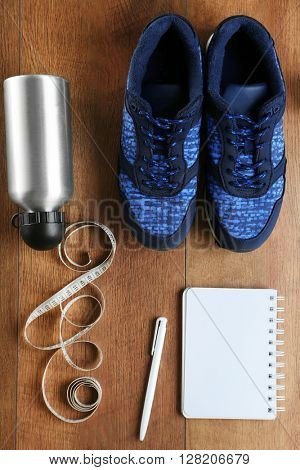 Athlete's set with female sneakers, bottle of water, equipment and notebook on wooden background