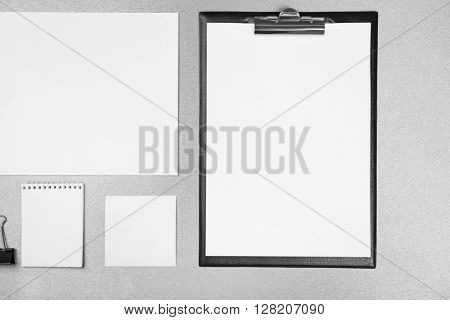 Office set with white sheets of paper, notebook and stationery on grey background