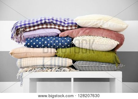 Set of warm plaids and pillows on white shelf against striped wall background