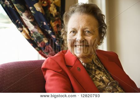 Elderly Caucasian  woman by window at retirement community center.