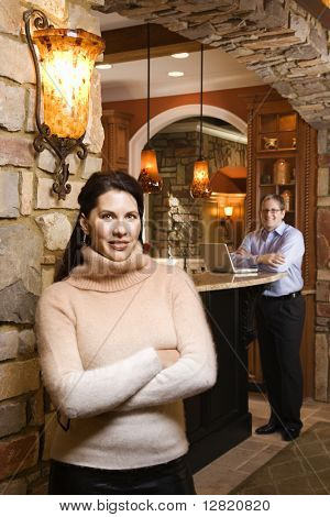 Caucasian woman standing with arms crossed looking at viewer with Caucasian man in background on laptop.