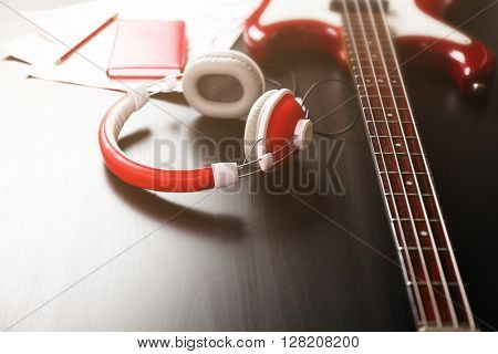 Electric guitar with headphones and notes on black wooden background