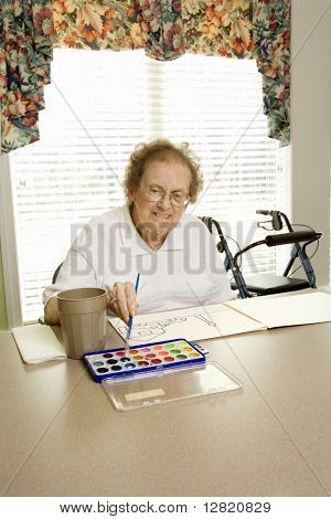 Elderly Caucasian woman painting with watercolors at retirement community center.