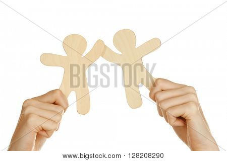 Hands holding a couple of wooden figures, isolated on white