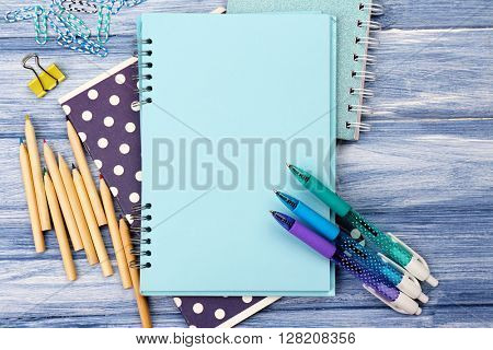 Office set with notebooks, colored pens and pencils on blue wooden background