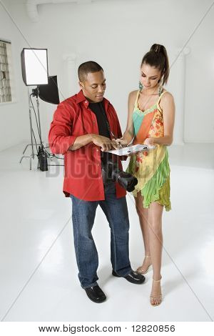 Afro americano joven fotógrafo adulto masculino sobre contrato con joven mujer caucásica de adultos