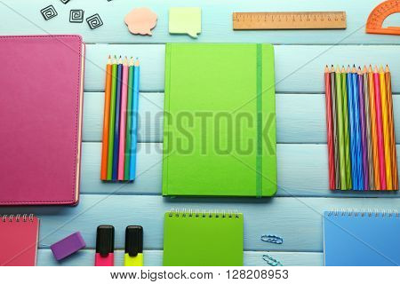 School set with notebooks and colored pencils on wooden blue background