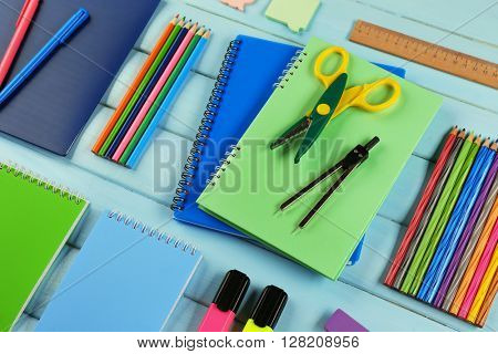 School set with notebooks, scissors and colored pencils on wooden blue background