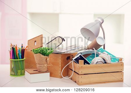 Wooden boxes with things for relocation on light table