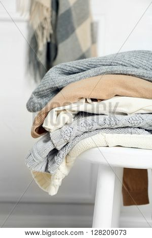 Pile of woolen clothes on white stool in a light interior