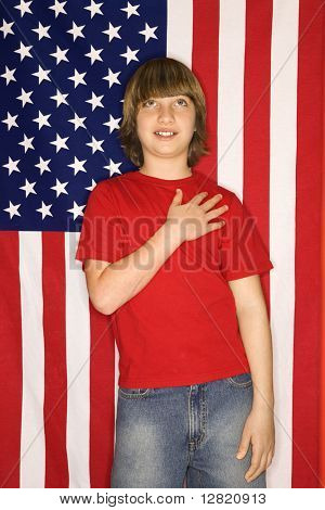 Portrait of Caucasian boy with hand over heart with american flag background.