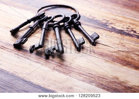 Bunch of old keys on wooden background, close up