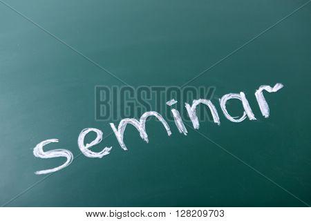 Seminar inscription written with white chalk on blackboard