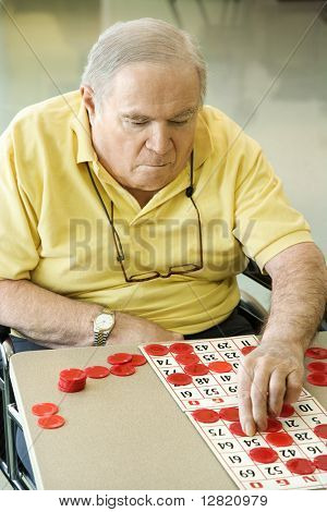 Elderly Caucasian man sitting in wheelchair playing bingo at retirement community center.