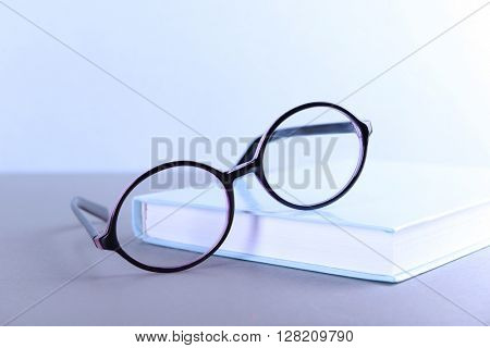 Books and eyeglasses on grey table against blue wall