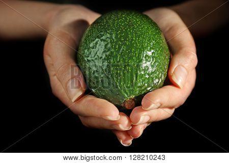 Female hands holding fresh avocado on black background