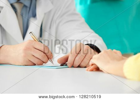 View on doctor's hands writing a prescription, close-up