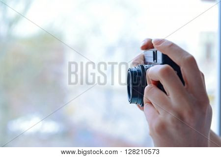 Female hands holding retro camera on light blurred background