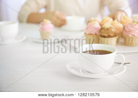 Female hands at the table with tea and cupcakes closeup