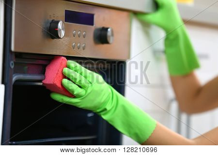 Woman hand in protective glove cleaning oven with sponge