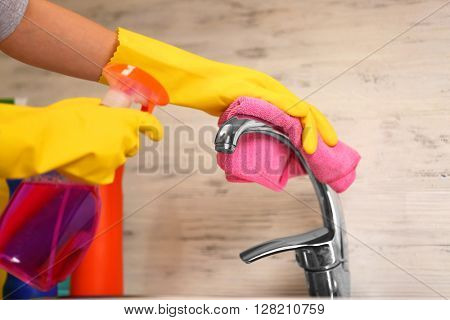 Female hands with rag and detergent spray cleaning a tap in the kitchen