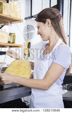Young Saleswoman Packing Cheese At Store