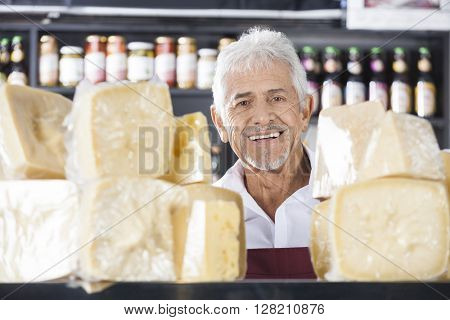 Confident Senior Salesman Smiling In Cheese Shop