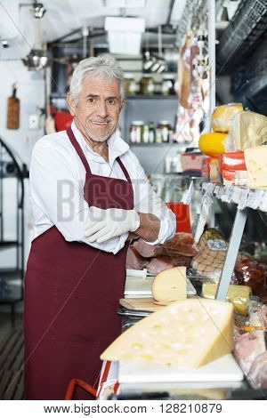 Confident Salesman Standing At Counter In Cheese Shop