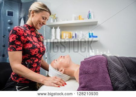 Beautician Smiling While Looking At Customer In Salon