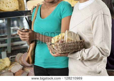 Couple With Cheese Basket In Grocery Store