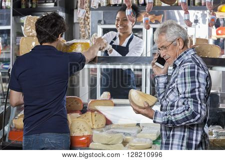 Senior Man Buying Cheese While Talking On Mobilephone