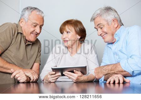 Senior Woman With Male Classmates Using Digital Tablet