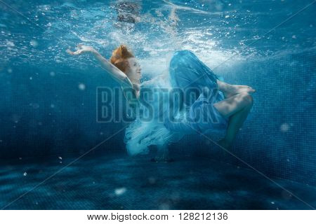 The girl from the fairy tale flounders in a blue dress under water.