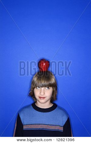 Head and shoulder portrait of Caucasian boy with apple on his head standing against blue background.