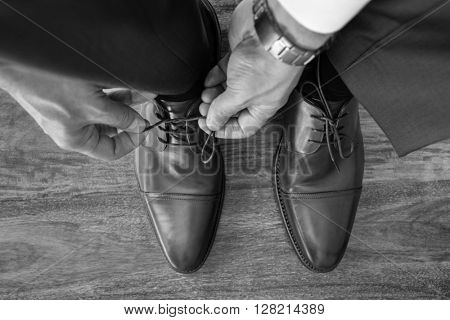 Businessman or groom tying shoe laces preparing for business meeting, interview or wedding