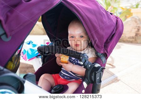 Cute baby girl in buggy on summer holidays in Spain