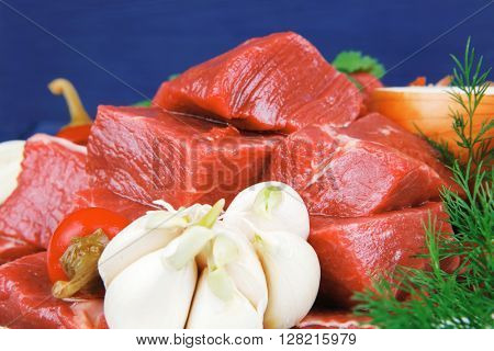 raw fresh beef meat slices in a white bowls with onion and red peppers serving on blue table with cutlery