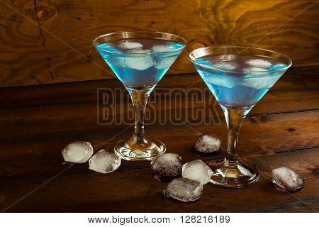 Two glasses of blue cocktail on dark wooden background. Blue Martini. Blue Hawaiian cocktail.