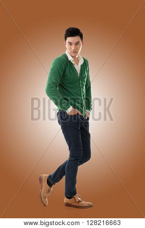 Handsome young Asian man with sweater, full length portrait isolated.