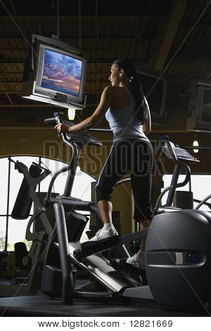 Prime adult Caucasian female on elliptical machine at gym.