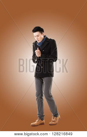Asian young man feel cold in the winter, full length portrait isolated