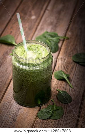 Healthy green smoothie with spinach, in a glass jar against a rustic wood background.