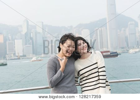 Asian happy young girls traveling at Victoria harbor, Hong Kong, Asia.