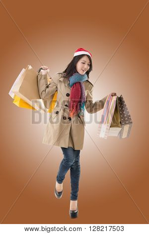 Happy shopping girl holding bags and gift box, wearing Christmas hat ,full length portrait isolated