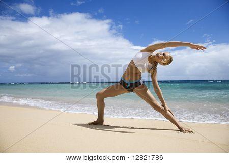 Kaukasische jonge volwassen vrouw die zich uitstrekt aan strand.