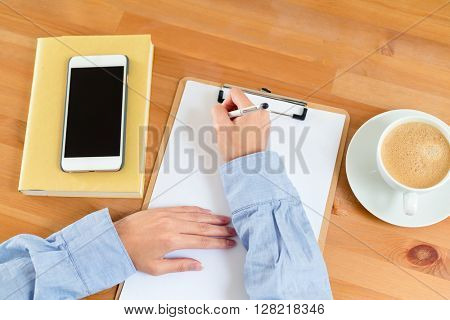Top view of woman writing on clipboard