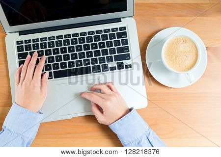 Woman wrking on notebook computer with coffee