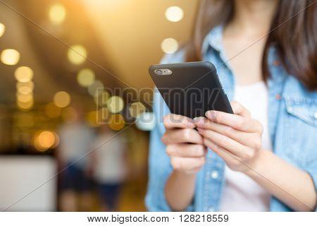 Woman sending text message on cellphone
