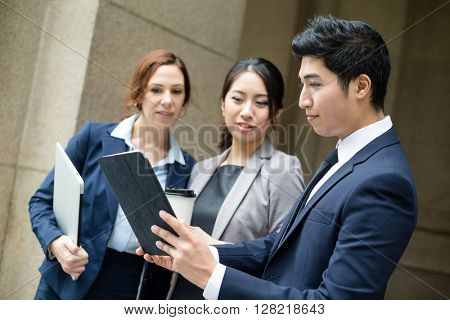 Business people discuss on tablet