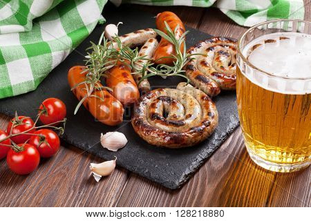 Grilled sausages and beer mug on wooden table